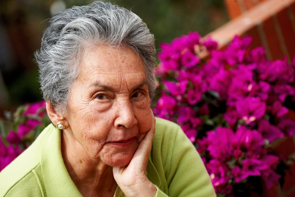 senior woman portrait with some flowers at the background